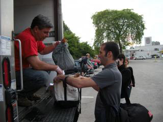 Steve Parkes of Cape Ann Fresh Catch hands fresh seafood to a CSF shareholder at the Morse School in Cambridge