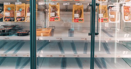 empty refrigerated meat section of grocery store